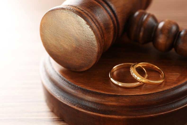 Immagine di un martello da giudice con due fedi vicino, a simbolo del ruolo dell'avvocato matrimonialista nel supporto di una coppia